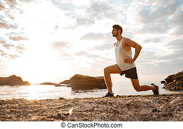 Young healthy man athlete doing squats at the beach at...