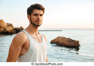 Young handsome man athlete standing at the rocky beach by...