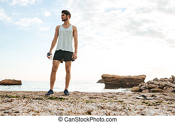 Man athlete resting after jogging at the beach - Young...