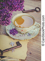 summer cup of tea with lilac flowers and vintage photos,...