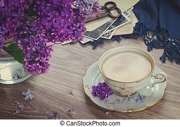 summer tea time - cup of tea with lilac and vintage photos,...