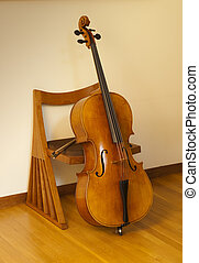 Cello or violincello, resting on chair with bow