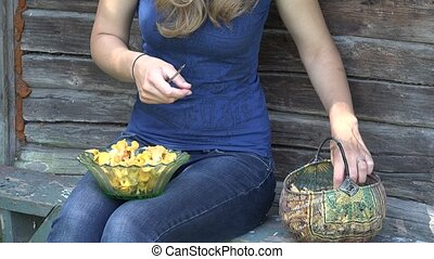 female villager hands with knife clean chanterelle...