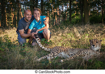 Young couple walking in the woods with cheetah