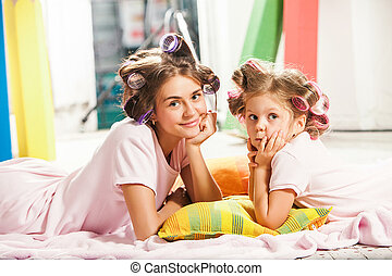 Little girl sitting with her mother and playing - Little...