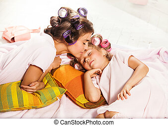 Little girl with her mother slipping in bed - Little girl...