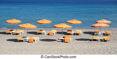 Greece. Kos island. Kefalos beach. Orange chairs and...