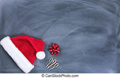 Erased black chalkboard with Santa cap and candy canes plus...
