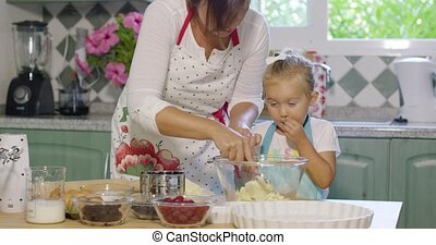 Cute little girl helping her mother bake mixing ingredients...