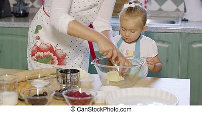 Mother teaching her small daughter to bake placing...