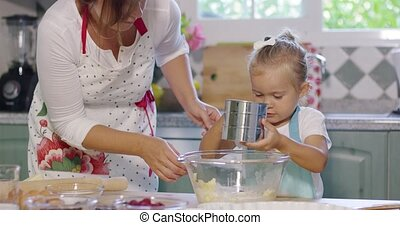 Pretty little girl helper in the kitchen helping her mother...