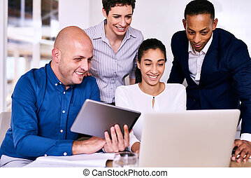 Group of diverse entrepreneurs looking at a computer and...