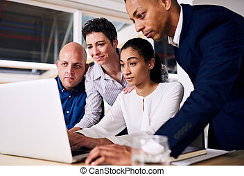 group of business partners looking at the same laptop screen...