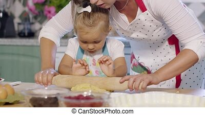 Mother rolling out pastry with a little helper as she...