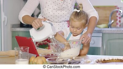 Cute little kitchen helper helping her Mum with the baking...