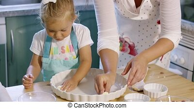 Cute little girl greasing a baking dish with a pat of butter...