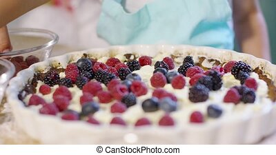 Little girl finishing off a homemade berry pie as she helps...