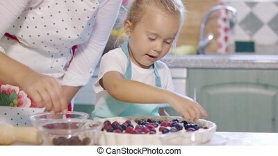Mother and daughter adding fresh berries to a pie