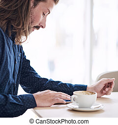 Trendy male hipster busy using his tablet on the table