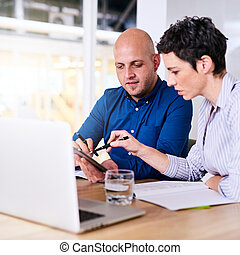 business man and woman working on their computer together -...