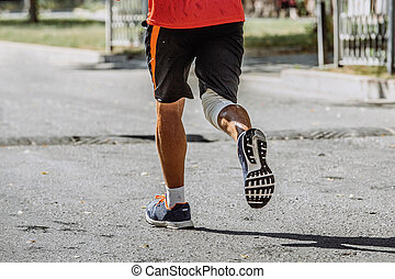 rear view of a man running through streets of city, at foot...