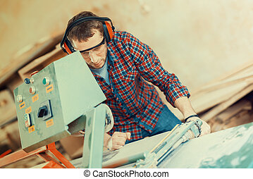 Carpenter with automatic circular saw. He has protective...