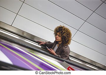 Leaving the subway - Woman travelling up an escalator from...