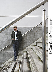 Businessman on Stairs - Businessman stood against the wall...