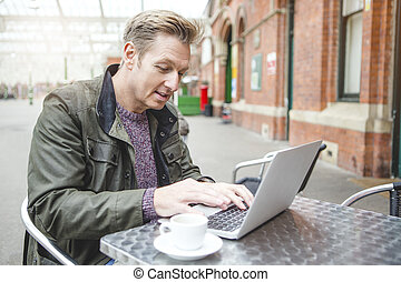 Working at the Train Station - Man using a laptop at a cafe....