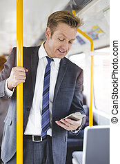 Businessman on the Train - Formal businessman standing on a...
