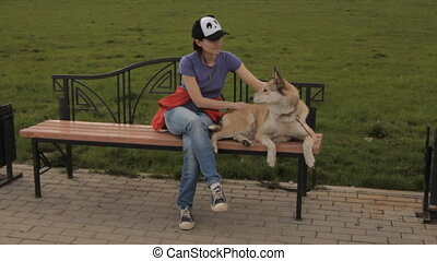 A girl sitting on a bench with a dog.