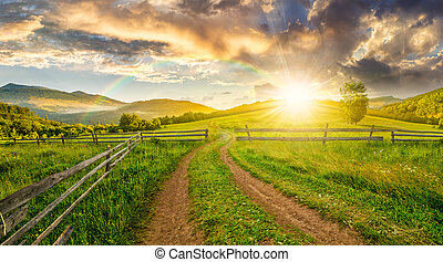 road and wooden fence on hillside at sunset