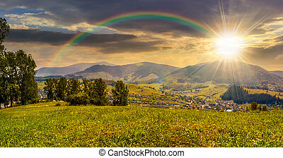 meadow near the village in mountain valley at sunset -...
