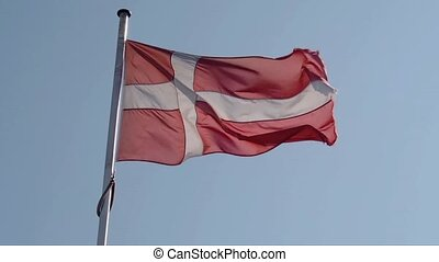 Waving Danish flag on a blue sky, retro film toned