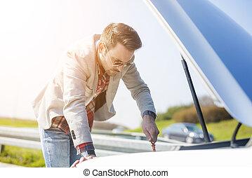 Side view of men checking motor oil