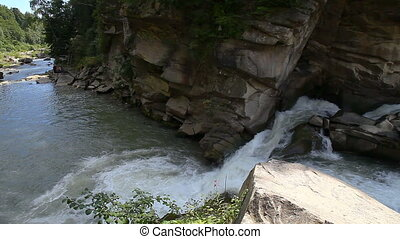 Strong mountain stream flowing over rocks - A river flows...