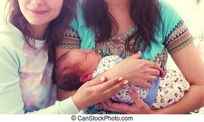 Mother holds newborn baby and photographed with girlfriend....