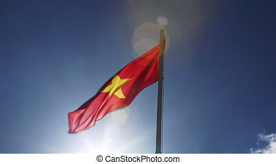 Textile flag of Vietnam in front of blue sky