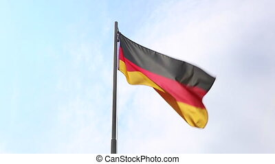 Textile flag of Germany on a flagpole in front of blue sky
