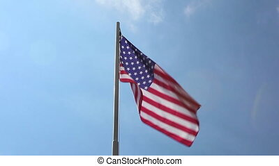National flag of United States in front of blue sky