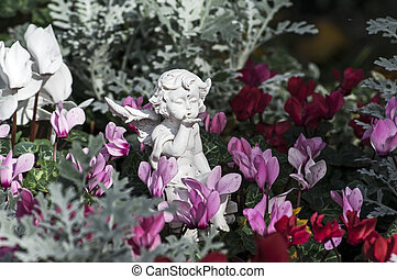 Porcelaine angel in a flower bed - Flowers and an angel