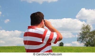 Man in a field look into binoculars