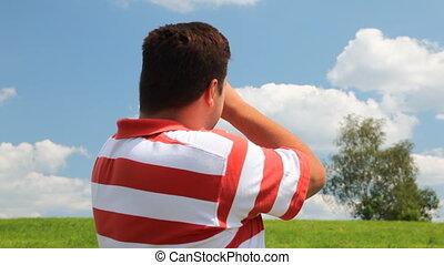 Man in a field look into spyglass