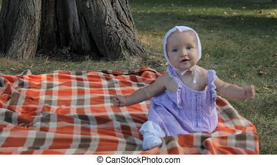 A baby girl sitting on a blanket and holding a stick