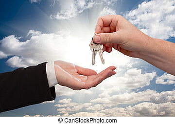 Male Handing Keys to Female Over Clouds and Rays - Male Hand...
