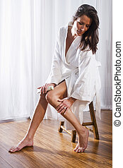 Beautiful brunette woman wearing bathrobe applying lotion to...