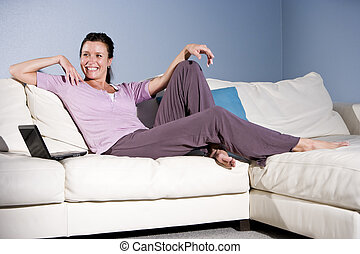 Happy woman relaxing on couch smiling with laptop - Happy...