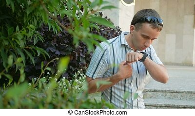 Outdoor portrait of modern young man with smart watch. Man...