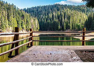 pier on mountain Lake - fence of wodden piere on the lake...
