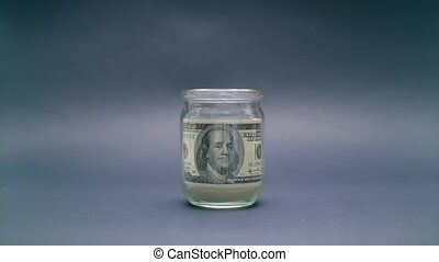 Hand Takes Money from Glass Jar - Woman Puts American Dollar...